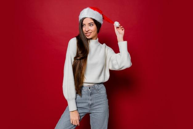 Счастливая женщина с удивительными длинными волосами в новогодней шапке позирует
