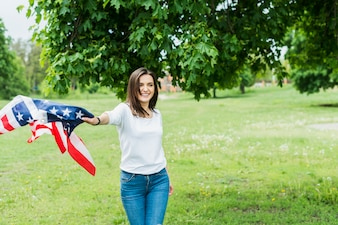 Happy woman with american flag in nature