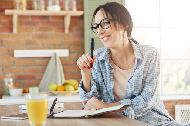 Happy woman with appealing appearance, going to organize party, makes list of invited friends, sits in kitchen,