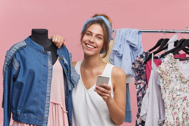 Happy woman with appealing appearance, standing near mannequin, having joyful expression while being glad to buy new outfit, typing messages to her best friend, sharing latest news with each other