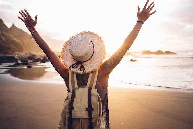 腕を持つ幸せな女は、夕暮れ時のビーチで自由をお楽しみください。