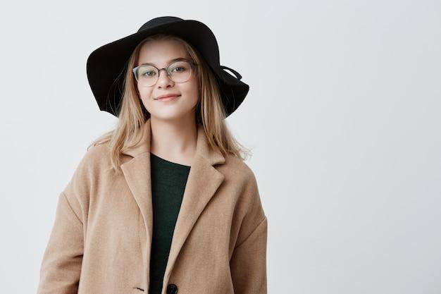 トレンディなコートと黒い帽子に身を包んだ眼鏡をかけた魅力的な外見の幸せな女性は、前向きな感情を表現し、友達と公園を散歩した後に休憩し、良い気分を持っています。