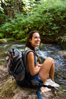 自然を探索しながら休んでバックパックで幸せな女