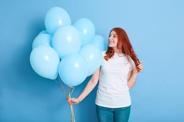 笑顔で彼女の贈り物を見て、彼女の髪に触れ、カジュアルな服装を着てプレゼントとして風船を持つ幸せな女性