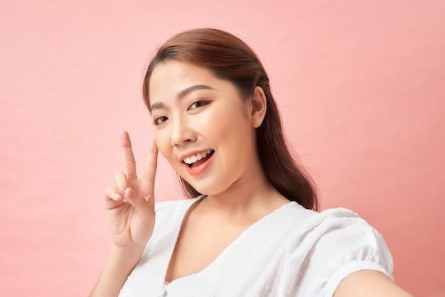 빛나는 미소 셀카를 만들고 분홍색에 대한 v 기호를 보여주는 행복한 여자
