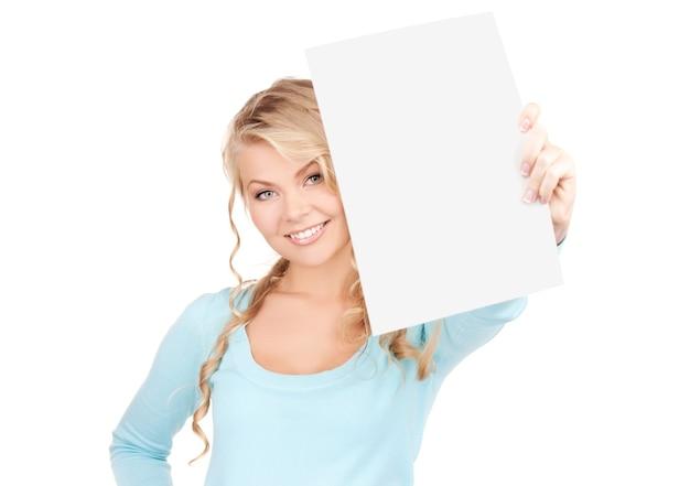 白い壁に空白のボードを持つ幸せな女
