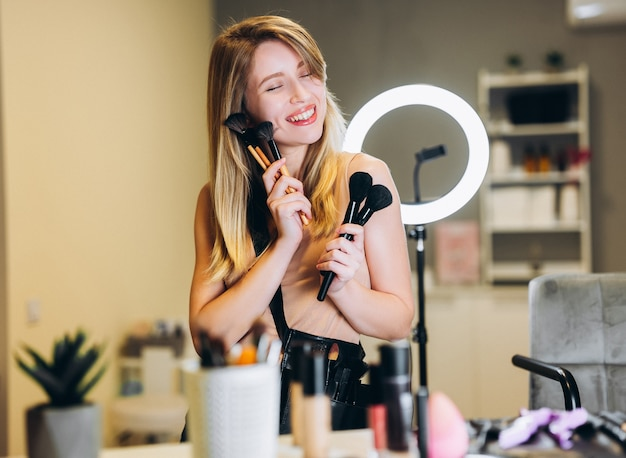 ブロンドの髪の幸せな女性は彼女の手に多くの化粧ブラシを持っています。顔の近くの化粧ブラシで笑っている金髪。