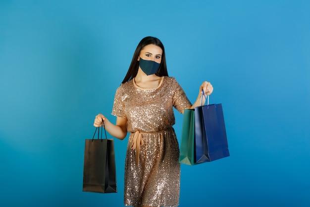 파란색 보호 마스크와 함께 행복 한 여자는 베이지 색 드레스를 착용하고 쇼핑 가방을 운반