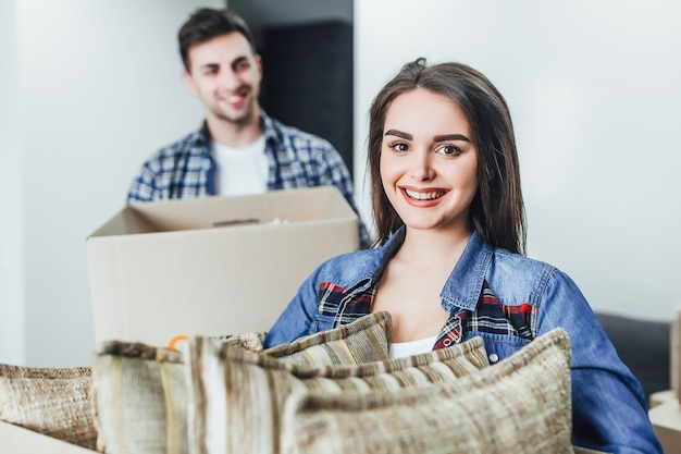 新しい家の手にボックスを持つ幸せな女性