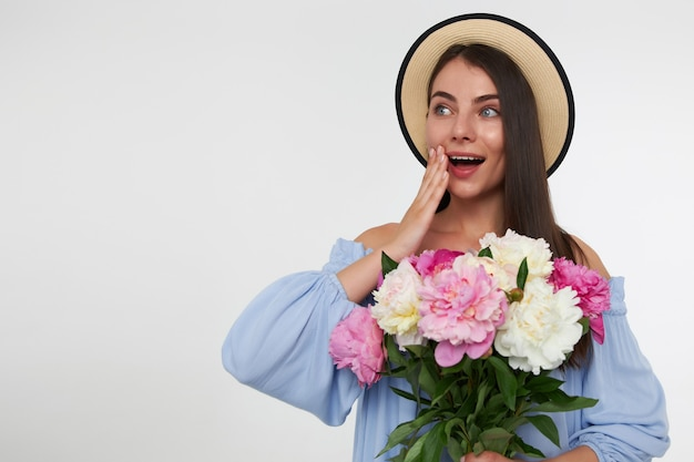 Happy woman with brunette long hair. wearing a hat and blue dress. holding bouquet of flowers and touching her cheek, surprised