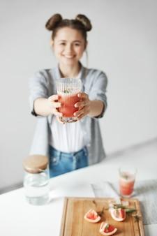 흰 벽에 스트레칭 자몽 해독 스무디 미소 빵 행복 한 여자. 건강한 다이어트 음식. 유리에 중점을 둡니다.