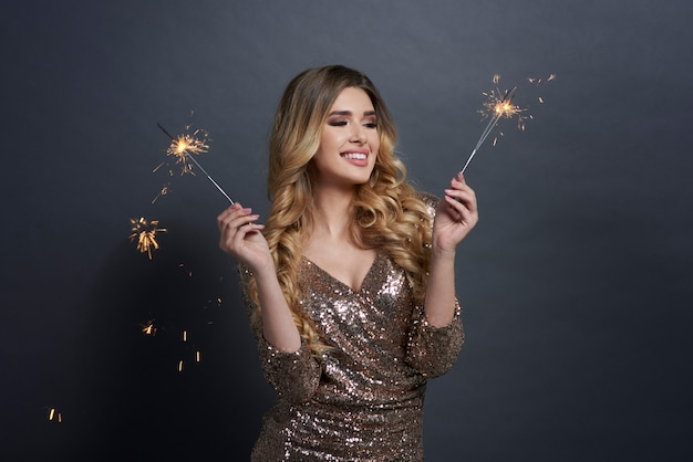 Happy woman with burning sparklers