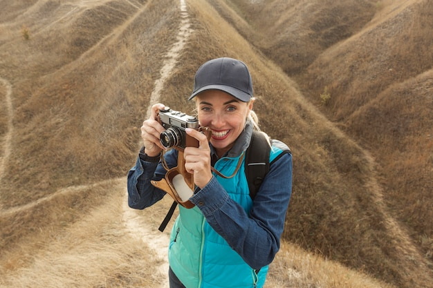 Happy woman with camera outdoors