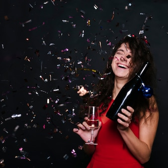 Happy woman with champagne bottle and glass