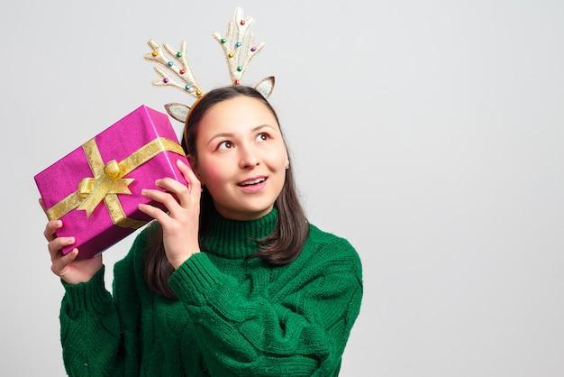 Счастливая женщина с рогами оленей рождества с подарком на белой предпосылке изолированной с космосом экземпляра.