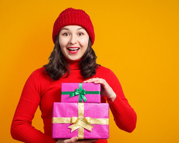 손에 크리스마스 선물 행복 한 여자입니다. 노란색 표면에.