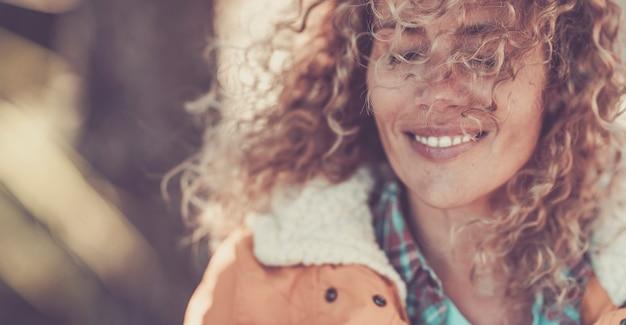 눈을 감고 만족하거나 만족하는 행복한 여성입니다. 곱슬머리와 모피 재킷을 입은 여성 여행자는 눈을 감고 생각에 잠겨 있습니다. 웃는 사려깊은 여자