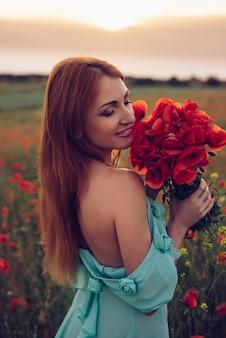 일몰, 클로즈업에서 양 귀 비의 꽃다발을 들고 닫힌 된 눈을 가진 행복 한 여자
