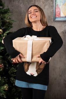 Donna felice con gli occhi chiusi che tiene un regalo di natale. foto di alta qualità