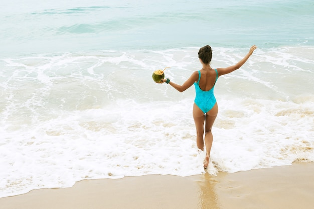 Happy woman with a coconut on the beach