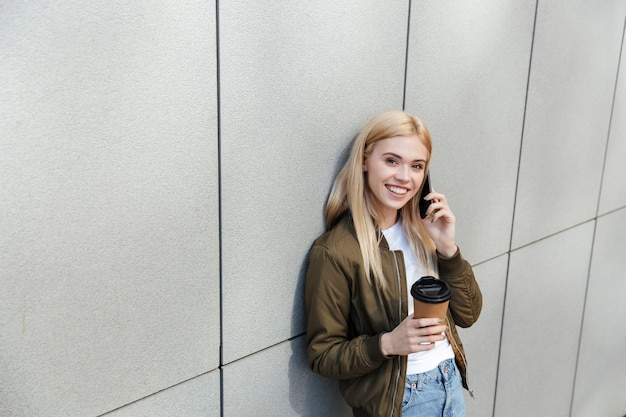 Happy woman with coffee talking on smartphone