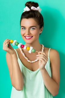 Happy woman with colorful makeup and sweet candies on skewer