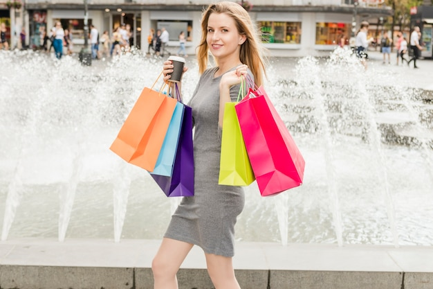 Happy woman with colorful shopping bags walking in front of fountain