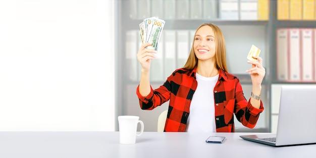 白い机の上にコーヒーと彼女のラップトップのカップとクレジットカードとドル紙幣を持つ幸せな女性