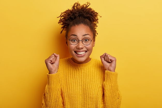 ぱりっとした髪の幸せな女性は、くいしばられた握りこぶしを上げ、目標を達成するにつれて明るいと感じ、広く笑顔で、アフロヘアーを持っています