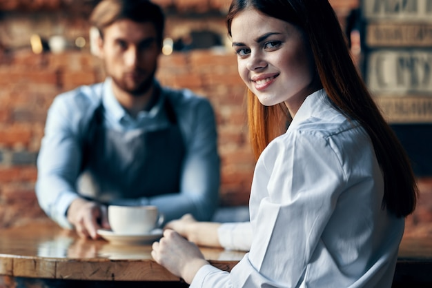Happy woman with cup of coffee and man bartender in apron