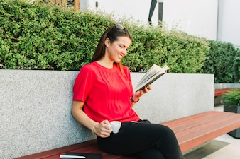 Happy woman with cup of coffee reading book