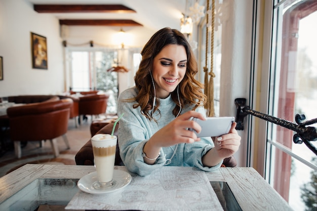 Happy woman with curls in cafe using smart phone and smiling