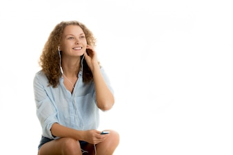 Happy woman with curly hair listening to music