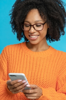 Happy woman with curly hair reading message, chatting in social media, isolated on blue