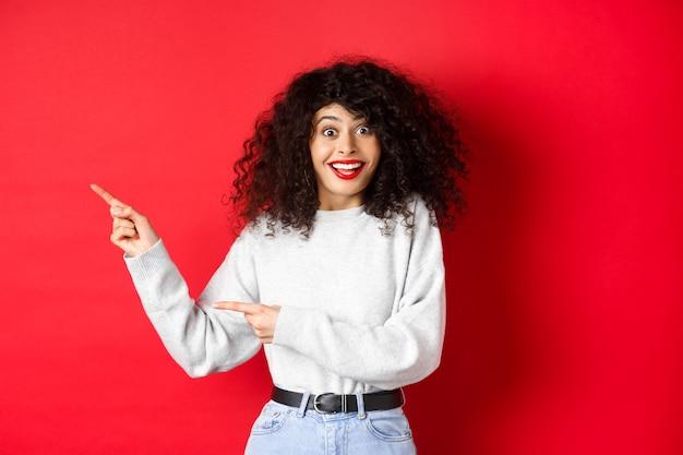 巻き毛、面白がって笑って、ロゴに残された指を指して、驚いて見える、特別な取引をチェックして、赤い背景の上に立っている幸せな女性。