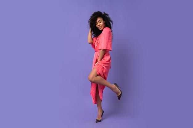 紫色の壁にポーズをとって巻き毛の幸せな女性。エレガントなパーティードレスを着ています。春のファッションルック。完全な長さ。