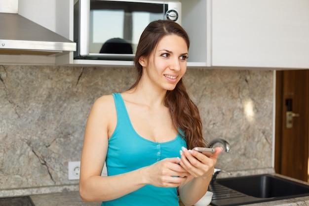 Una donna felice con i capelli scuri sta scrivendo messaggi al telefono in cucina