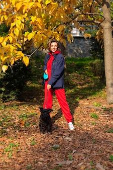 Donna felice con il cane nel parco con foglie autunnali