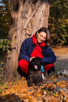 Happy woman with dog in park with autumnal leaves