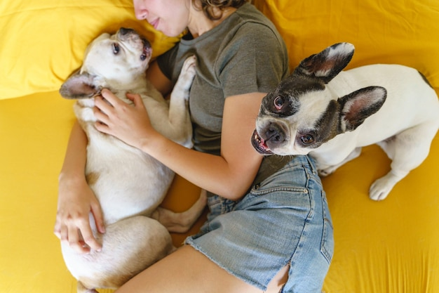 Happy woman with dogs in bed. top view of unrecognizable woman hugging couple of french bulldogs at home.