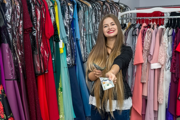 Happy woman with dollar banknotes in dress store