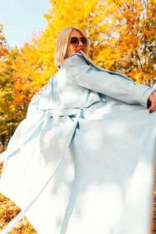 スタイリッシュな青いコートを着たファッショナブルなサングラスと幸せな女性は、明るい黄色の紅葉で自然の中を歩きます