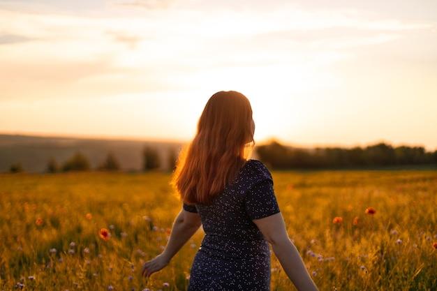 Счастливая женщина с цветами, наслаждаясь закатом в поле. концепция туризма, путешествий и здорового образа жизни.