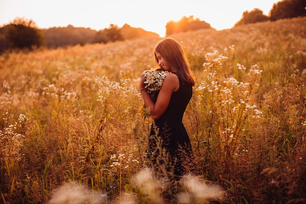 Happy woman with flowers stands on the evening field