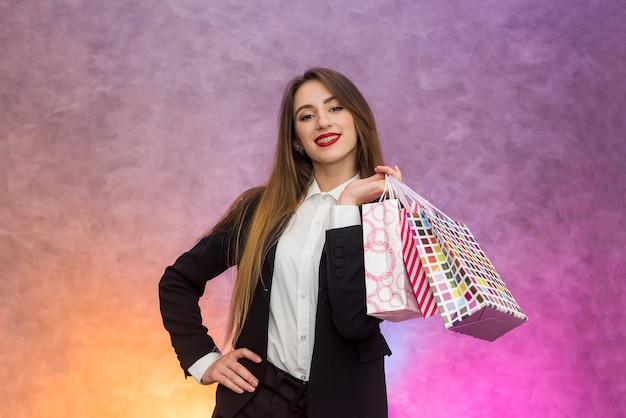 Счастливая женщина с подарочными пакетами улыбается