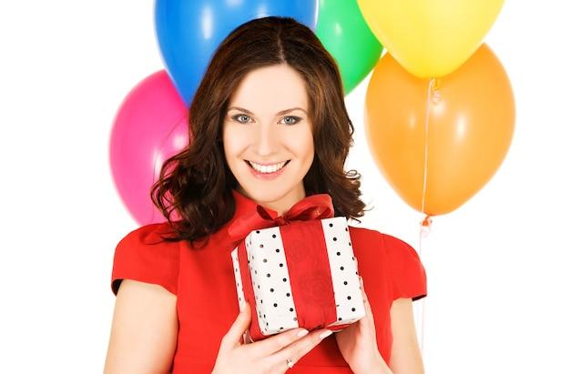 Счастливая женщина с подарочной коробкой и воздушными шарами