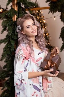 クリスマスツリーの近くにギフトボックスと幸せな女性