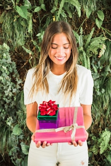 Happy woman with gift boxes standing against green leaves background