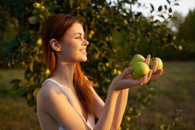 牧場の樹の近くの自然の中で彼女の手に青リンゴを持つ幸せな女性
