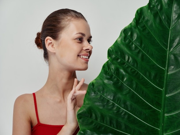 Happy woman with green leaf of palm tree red tshirt light background model